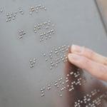 Två fingrar känner sig fram över en silverfärgad metallplatta som innehåller punktskrift