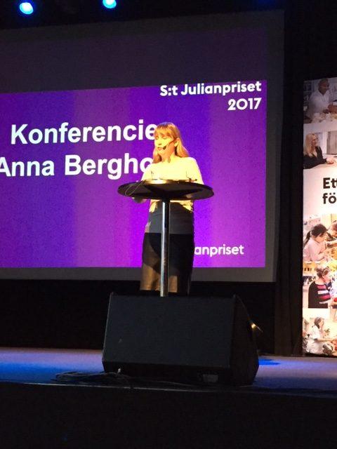 Från utdelningen av årets S:t Julianpriset. Jag som konferencier. I bakgrunden syns en skärm med text. Jag bär svart kjol och vit tröja.