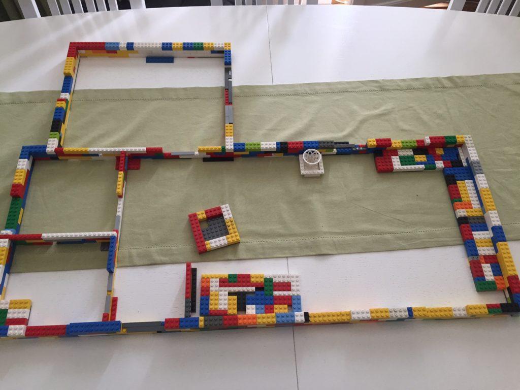 Färgglada legoklossar som ligger på ett bord och formar konturen på ett hus.