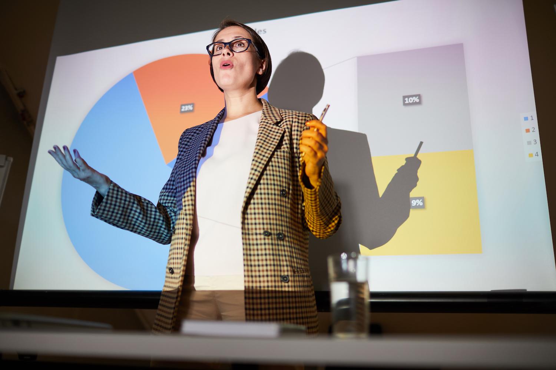 En kvinna med brunt kort hår föreläser nära en upplyst projektorduk. På duken syns olika procenttal i någon form av statistisk illustration.