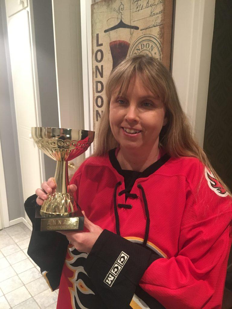Anna iklädd röd hockeytröja med vinnarpokalen för Annas Championship.