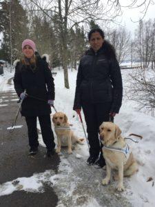 Jag och Mariah med våra ledarhundar i snön. Vi bär mörka vinterkläder och jag en rosa mössa.
