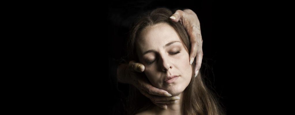 """Pressbild från """"Dom blinda"""". Ett ansikte med en kvinna som blundar. Runt ansiktet ser man två händer mot en svart bakgrund."""