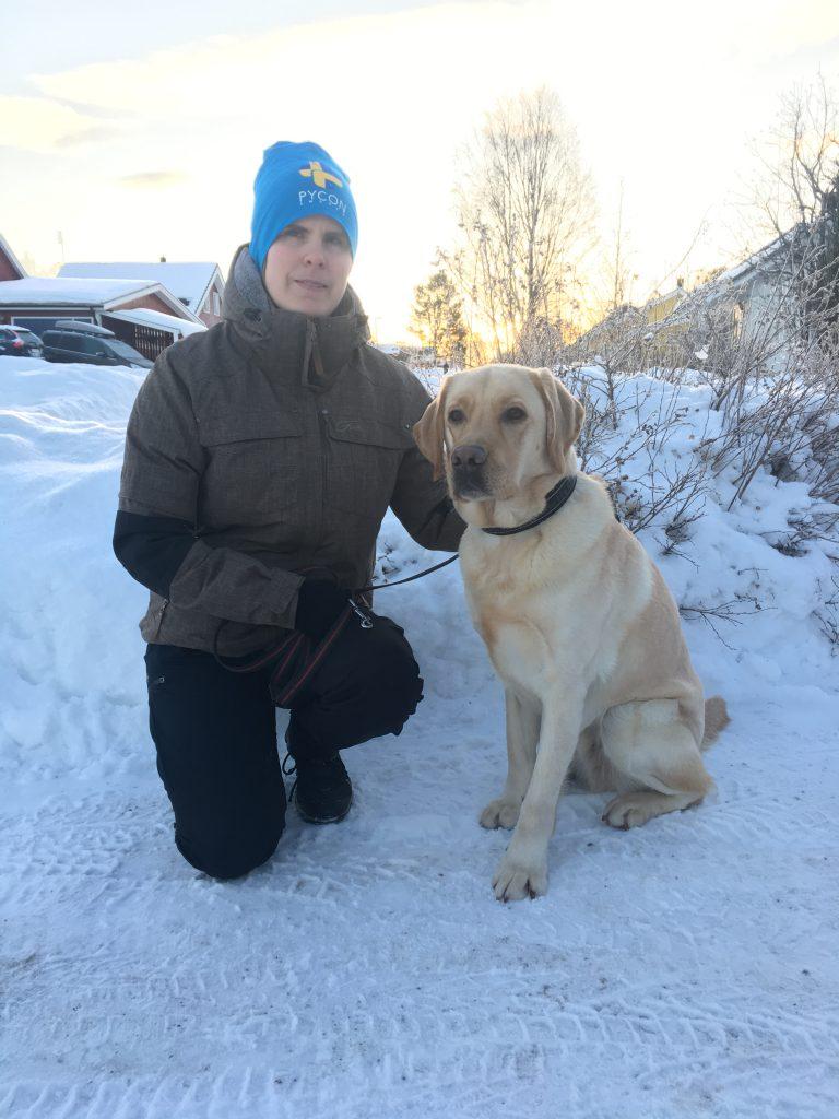 Ida med sin nya ledarhund, en gul labrador. Ida har blå mössa och grön jacka. De står i ett snöigt vinterlandskap.