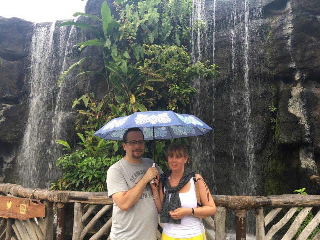 Jag och Magnus. Vi står med paraply framför en stenvägg och ett vattenfall rinner nedför väggen. Magnus har grå t-shirt, skägg och kort brunt hår. Jag har mörkblond lugg, vitt linne och gul nederdel.