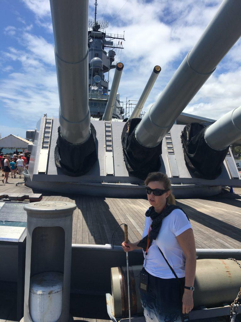 Jag framfår grå kanoner på slagskeppet Missouri. Jag håller i en vit käpp, bär vit t-shirt och solglasögon.