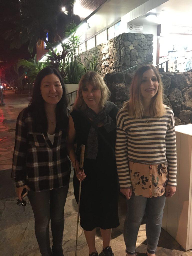 Bild från vänster: Jenny, jag och Laurie. Vi står utomhus en kväll, Jag har vit käpp, mörk klänning. Jenny har svart långt hår och bär rutig skjorta, mörka jeans och Laurie har blont långt hår, randig tröja och ljusblå jeans.