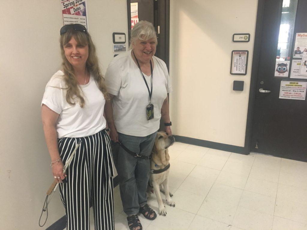 Jag tillsammans med Ann och hennes ledarhund i korridoren på the Windward community Colege. Vi bär vita tröjor, jag har mörkblont hår, svartvitrandiga byxor och Ann har grått hår, gråa byxor. Hunden till höger har ljus päls.