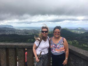 Jag och Annette Tashiro vid Utsiktsplatsen Nu'uanu Pali State Wayside. Man ser berg i bakgrunden en molnig dag. Vi står framför ett staket av äldre typ. Jag bär vit topp, svartvit-randiga byxor, solglasögon och vit käpp. Annette har gråsvart kort hår och bär mosaikmönstrad färgglatt linne och svarta byxor.