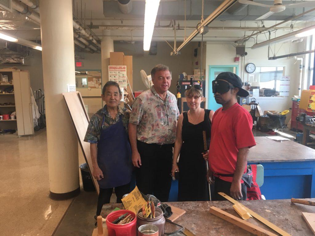 Foto när jag besöker Division of Rehabilitation/Service for the blind. Här i verkstaden med Dean, läraren och en student som bär mörklagda glasögon.