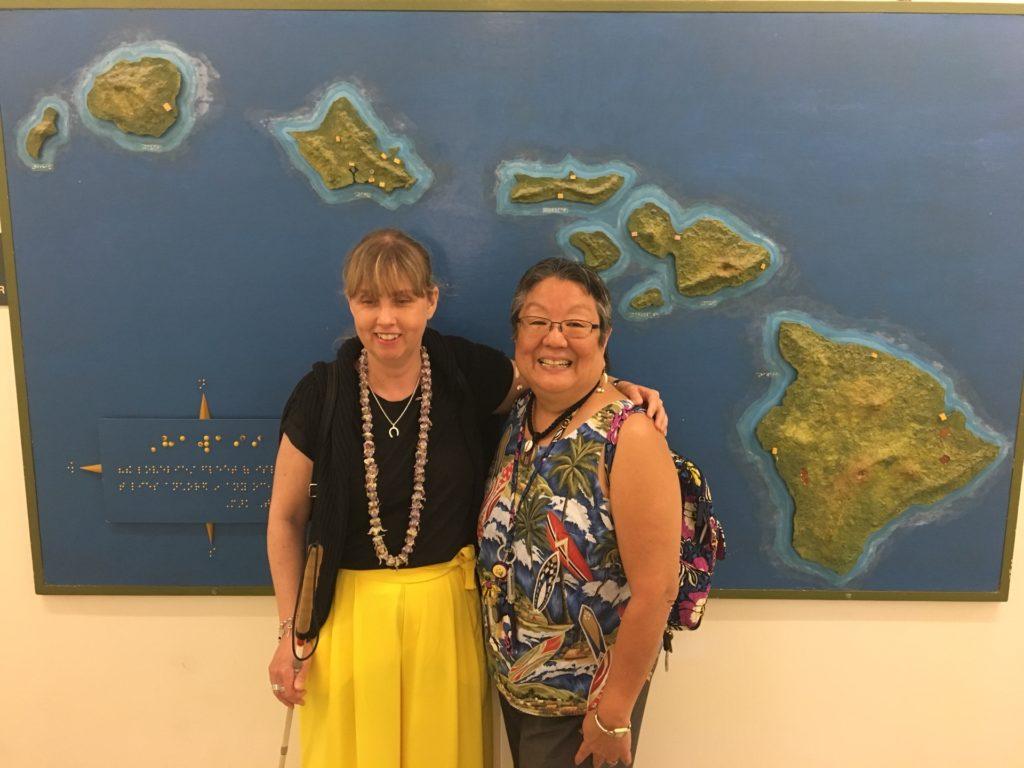 Jag och Annette som jobbar inom Independent Living. I bakgrunden syns den taktila kartan över Hawaii. Jag har på mig gula byxor, långt halsband med olika träkulor på, svart tröja och håller i min käpp. Anette bär linne med illustration av palmer och strand. Jag har ljusblont långt hår och Anette svartgrått hår.