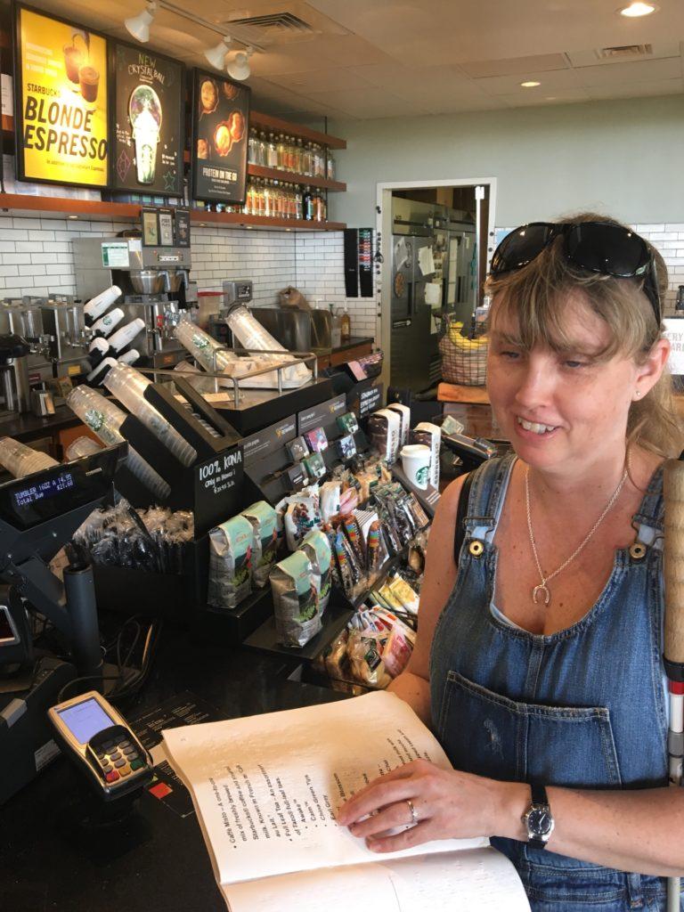 Jag med punktskriftsmenyn på Starbucks. Jag bär jeansbyxor med hängslen, långt mörkblont hår och solglasögon. I bakgrunden syns en restaurang med olika kaffepåsar på ett bord.
