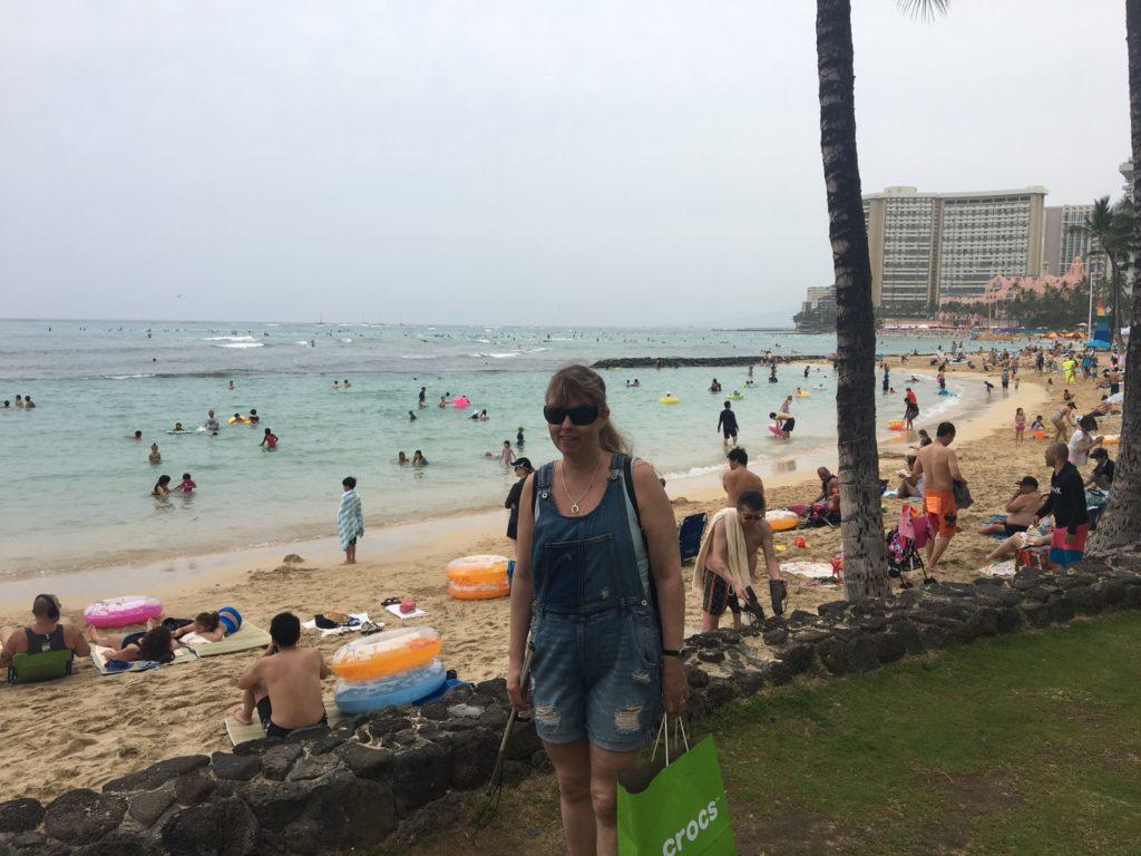 Jag på stranden på Waikiki, Jag har hängselbyxor i blått jeanstyg, håller i en käpp och en grön shoppingbag. I bakgrunden syns en sandstrand, människor och ljusblått vatten.
