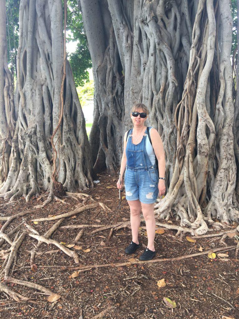 Jag i parken framför et stort träd. Grenarna slingrar sig om varandra likt ett sagoträd. Jag har på mig blå hängselbyxor av jeanstyg samt solglasögon.
