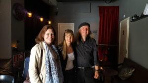 Jag, Ulf och Maria Acrén står i ett lite mörkt rum med rötda draperier. Maria har ljus jacka, brunt hår, jag vit topp, svart jacka, Ulf svart skjorta och svart basker.