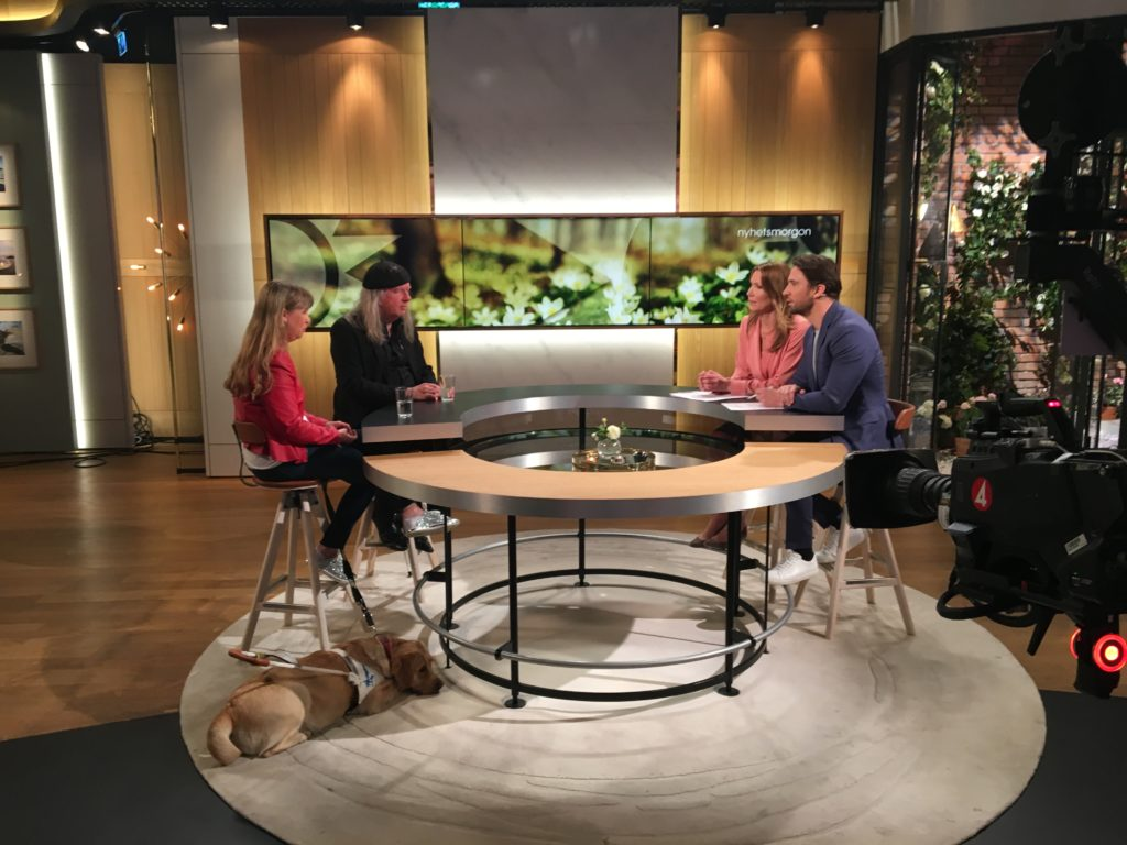 Studion i TV4 Nyhetsmorgon. Vi sitter runt ett cirkulärt modernt träbod. Jag har röd tröja och Ulf har svarta kläder och basker. Två programledare sitter mitt emot, kvinnan har ljusrosa tröja och mannen har blå kavaj.