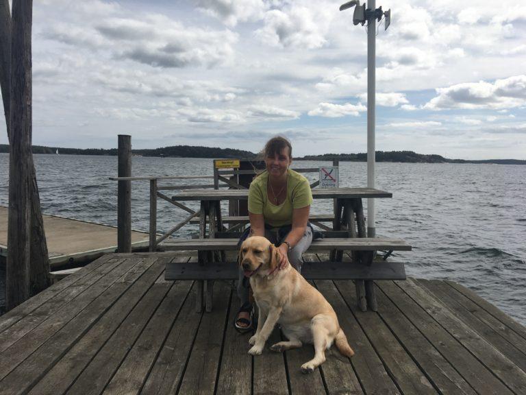 Jag med min ledarhund Chanti. Vi sitter en sommardag på en bänk intill vattnet på ett trädäck.