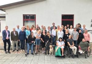 Gruppbild, Sommarskolan 2018. En stor grupp människor står framfår en vit husbyggnad.