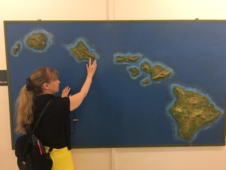 Jag håller handen på en taktil kartan över Hawaii. Kartan har blått vatten och gröna öar. Jag bär svart tröja och gula byxor.