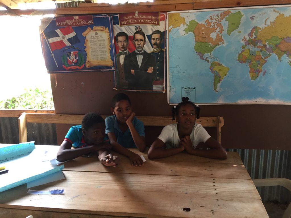 Tre elever i ett klassrum med en världskarta bakom.