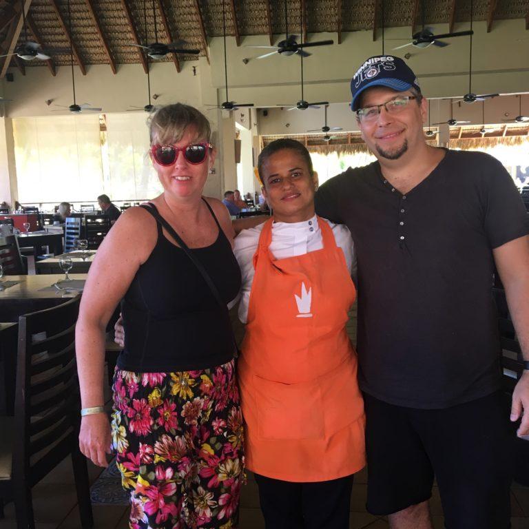 Jag, Martin och Ingrid som arbetar som servitris på vårt hotell. Jag har på mig blommiga byxor, svart topp. Ingrid har svart hår, orange förkläde, Martin har blå keps, svart tröja och byxor. Vi står i en offentlig restaurangmiljö.