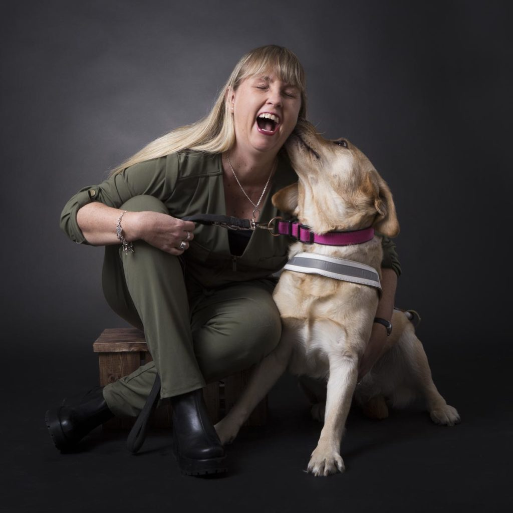 Jag och min ledarhund, en ljus labrador med vit sele. Jag är klädd i grön byxdress och sitter på en träpall i en fotostudio med grå bakgrund.