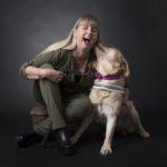 Anna och ledarhunden Chanti. Anna har grön tröja och gröna byxor och hunden har ljus päls med ett rosa koppel. Anna sitter på en träpall i en fotostudio med grå bakgrund.
