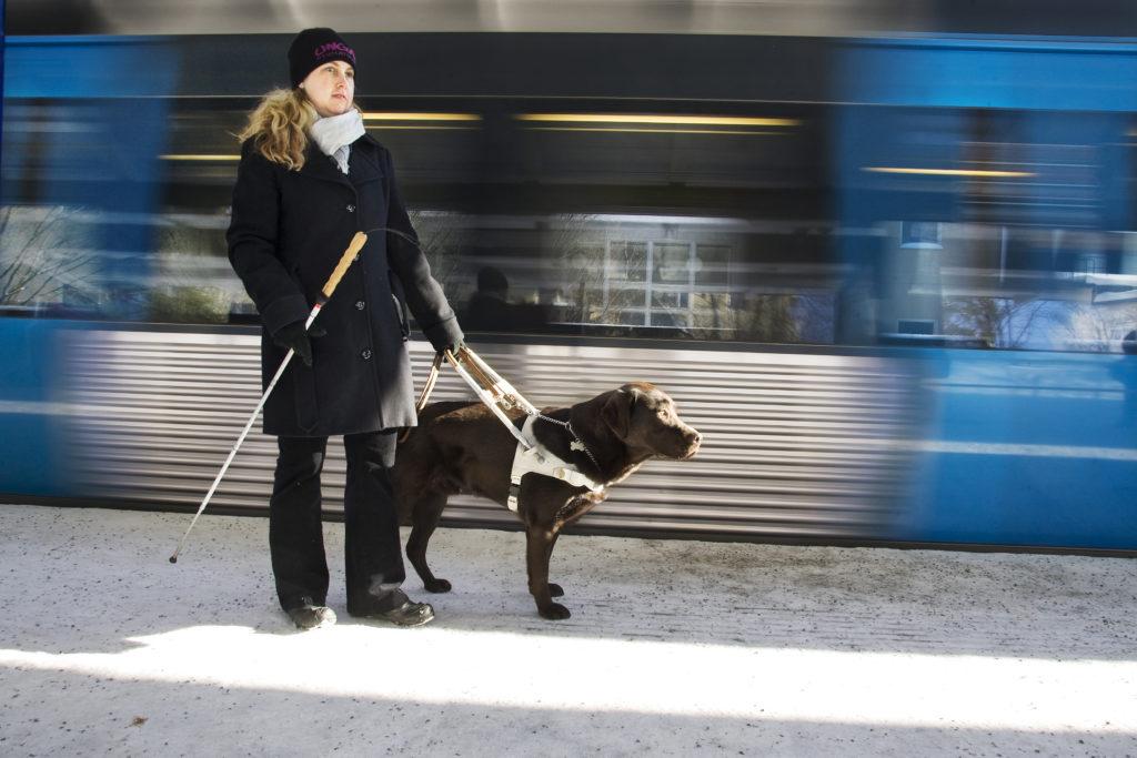 Vinterbild. Anna iklädd svart jacka och mössa på tunnelbaneperrongen med sin ledarhund, en brun labrador iklädd vit sele.
