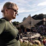 Helena i profil med headseet och mikrofon vid kinden samt sladdar kopplade till en sändare hängandes på bröstet. Helena är blond med uppsatt hår i knorr , är iklädd grön tröja och bär glasögon. På bilden syns även utomhusscenen i Pildammsparken i Malmö. Scenen omgärdas av läktare, typ amfiteater och det är nästan fullsatt.