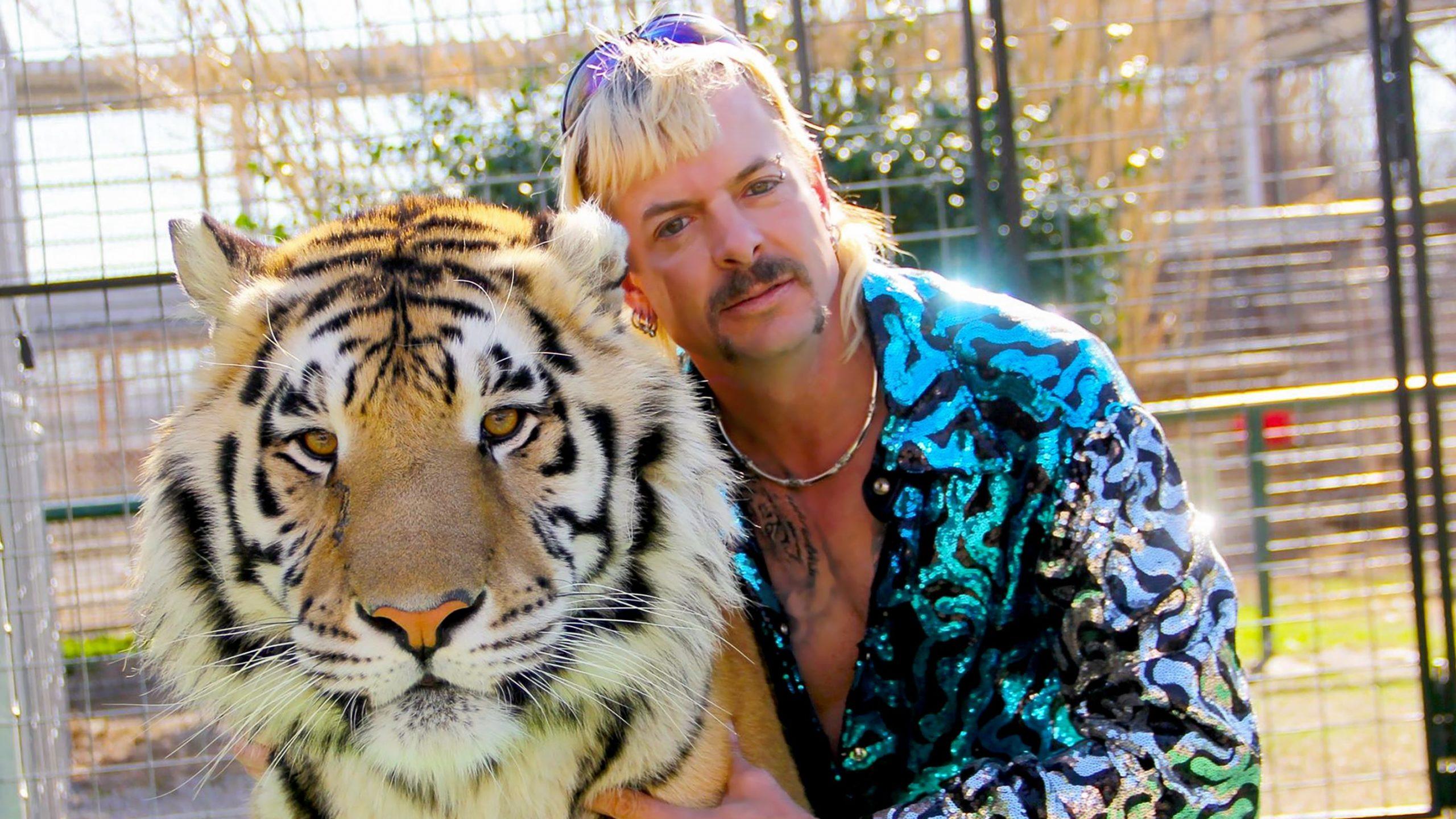 Bild på Joe Exotic intill en tiger med stängsel bakom.
