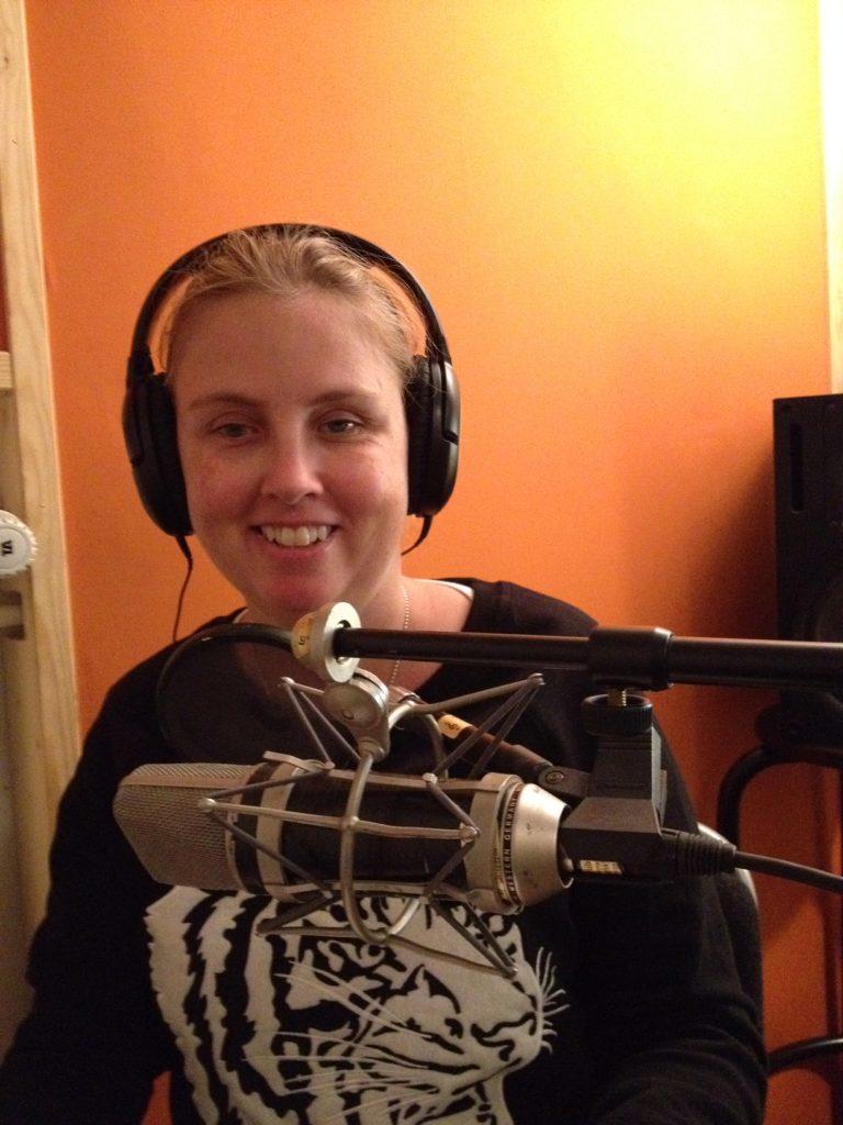 Jag i studion med hörlurar framför mikrofon