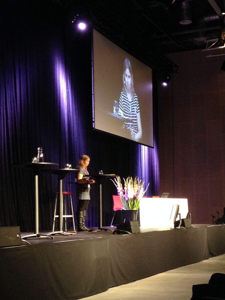 Jag som moderator på en stor scen med en projektorbild bakom. Jag har på mig em mörktvitrandig kjol, svarta stövlar och strumpbyxor.