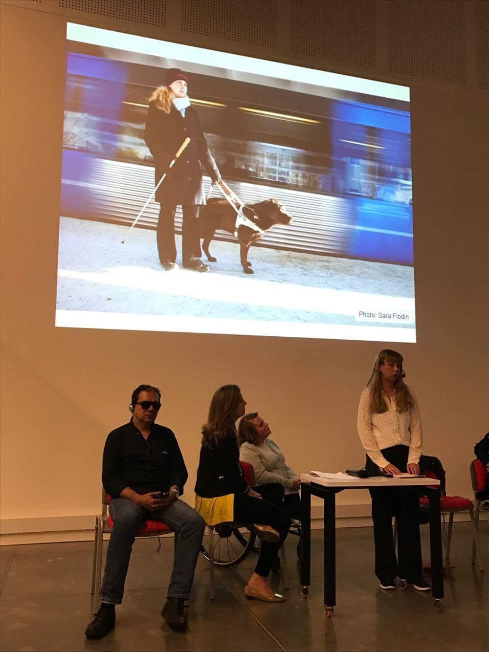Jag föreläser iklädd ljus skjorta med projektorbild i bakgrunden. Bilden visar mig med brun ledarhund på tunnelbaneperrong.