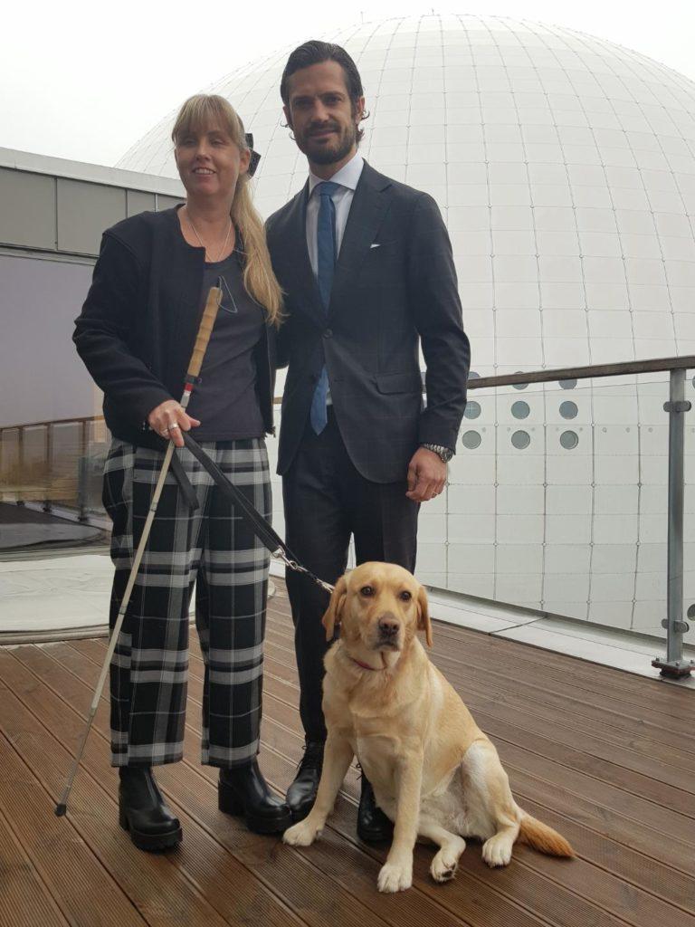 Jag tillsammans med Prins Carl Philip och min ledarhund, en ljus labrador. I bakgrunden syns Globenarenan. Jag är iklädd mörk överdel och rutiga byxor, Carl Philip är klädd i mörk kostym.