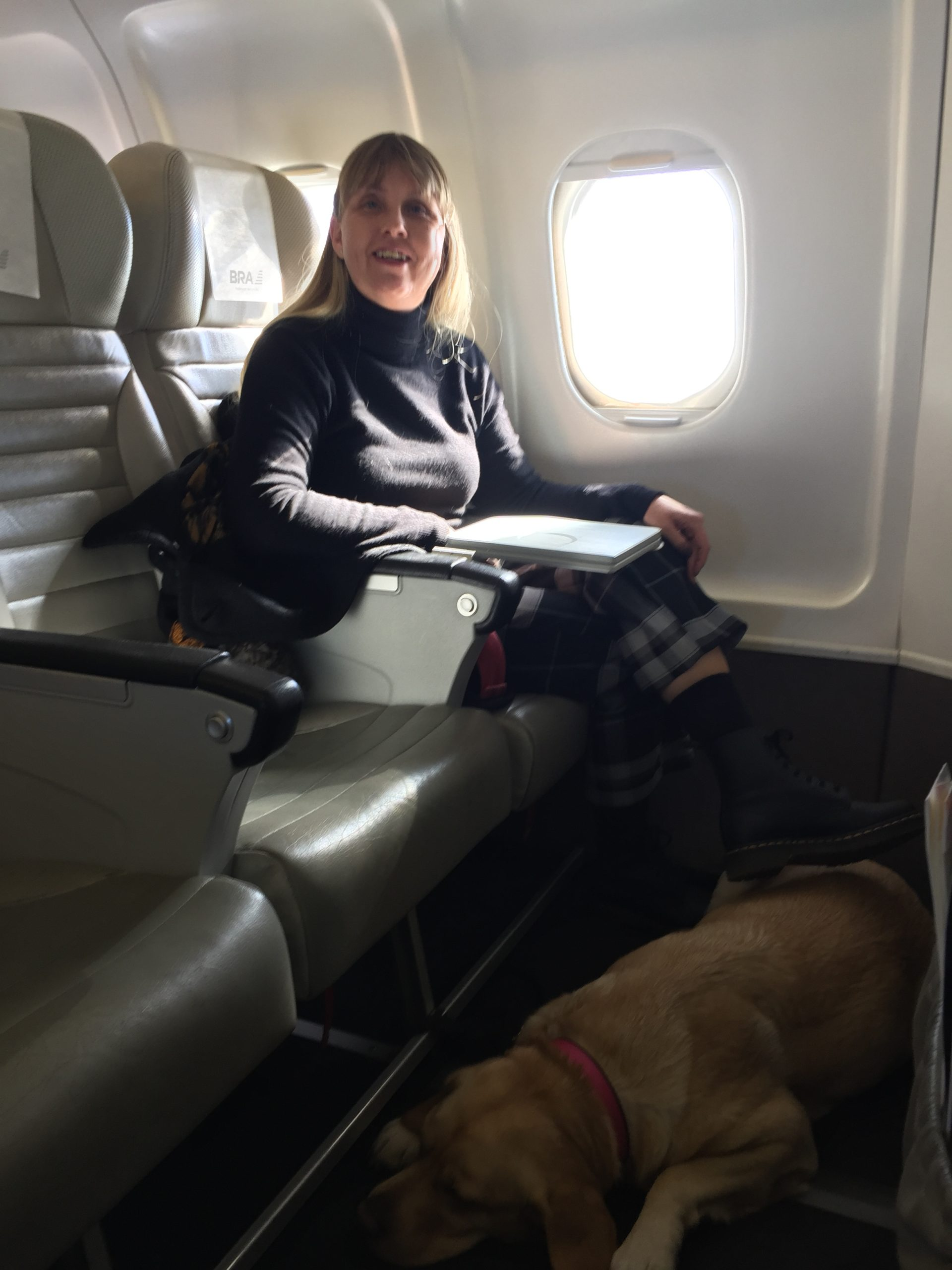 Jag sittandes längst fram i flyget med min ledarhund, en vit labrador som ligger på golvet framför sätet. Jag är iklädd svart polotröja och kjol.
