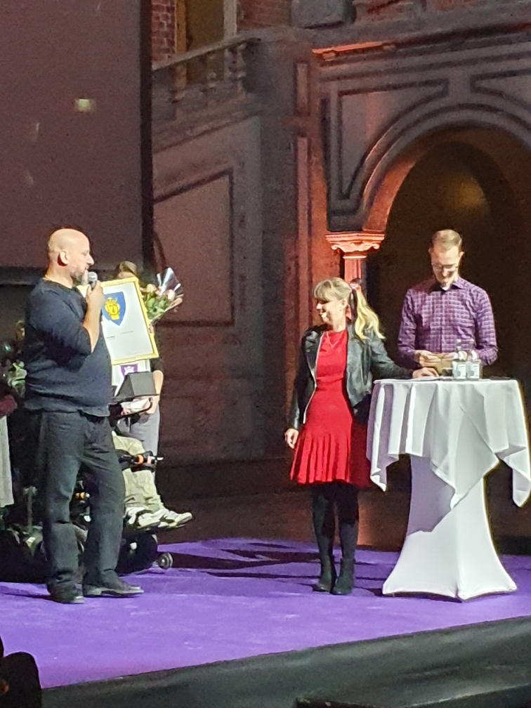 Jag på scen bredvid ett vitt ståbord. Till höger om mig står Jan Jönsson, Socialborgarråd i Stockholm. Vi lyssnar på Håkan Leydner till vänster som pratar i mikrofon. Jag är klädd i en röd klänning under svart skinnjacka samt svarta strumbyxor och skor.