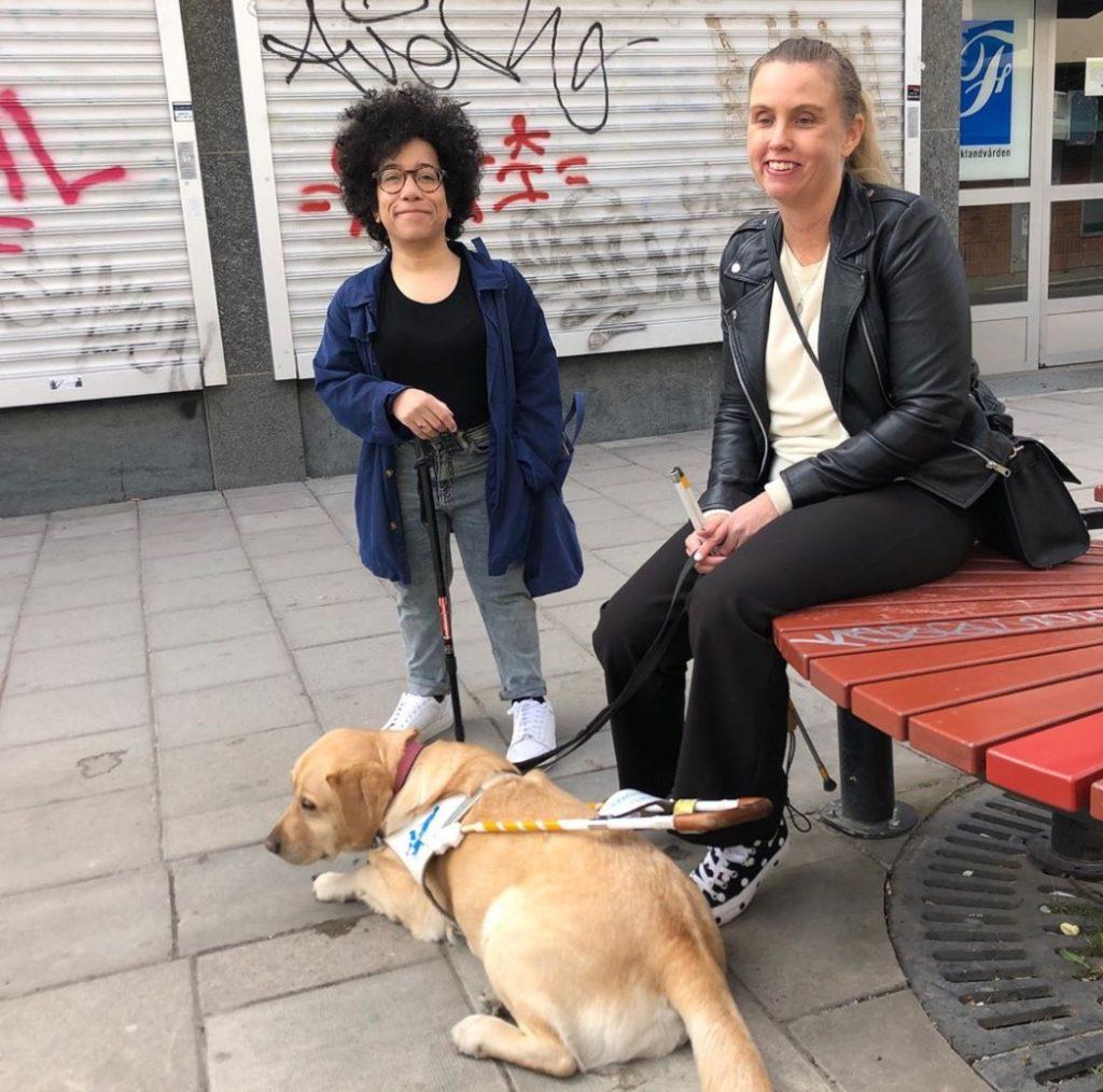 Jag sitter på en röd bänk utomhus intill Catrine Lundell. På marken ligger min ledarhund Chanti, en ljus labrador. I bakgrunden syns metallgardiner nedrullade över fönstren på en allmän lokal. På metallytan syns grafittitext i svart och rött. Jag har på mig svart skinnjacka, svarta byxor svartvita skor och en ljus tröja. Catrine är klädd i blå jacka, svart tröja och gråblå jeans samt vita skor.