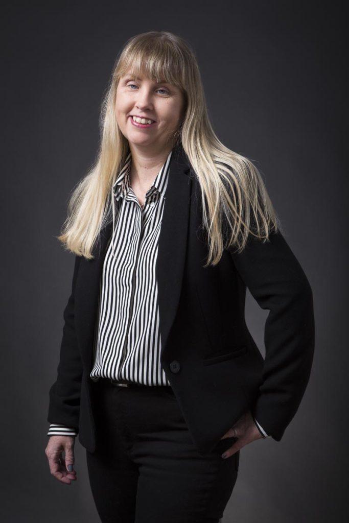 Anna Bergholtz har blont långt hår och har på sig en svartvitrandig skjorta med svart kavaj och svarta kostymbyxor.