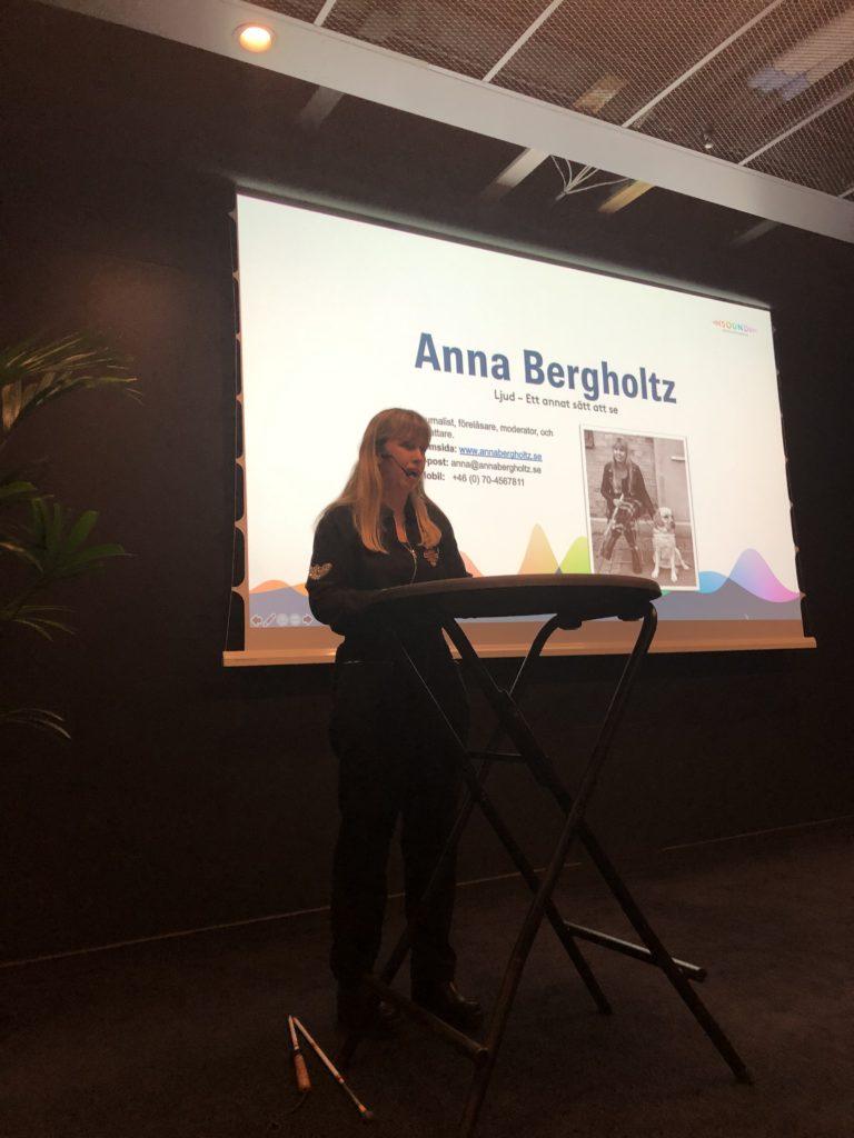 """Jag föreläser vid ett ståbord på en scen, iklädd svart byxdress. På en skärm i bakgrunden syns en bild på mig där jag sitter med min ledarhund och rubriken """"Anna Bergholtz""""."""