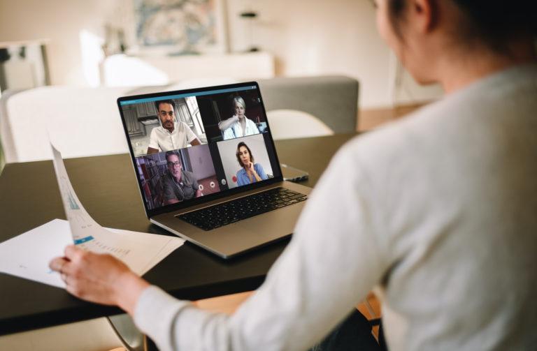 Tjej klädd i ljus tröja och mörkt hår sitter framför dator. På skärmen syns fyra ansikten som deltar i ett videomöte.