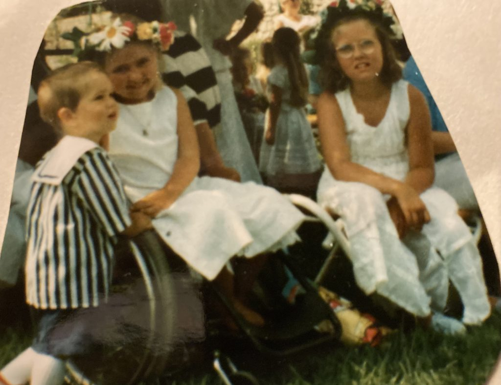 Ida i sin rullstol och jag bredvid. Klädda i vita sommarklänningar, bärandes midsommarkransar. Lillebror Victor klädd i blåvit-randig tröja.