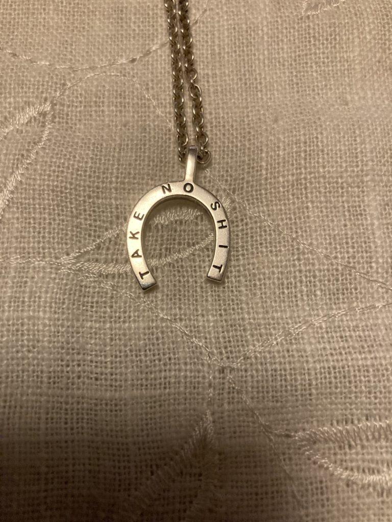 Halsband i silver, formad som en hästsko. På hästskon står Take no shit.