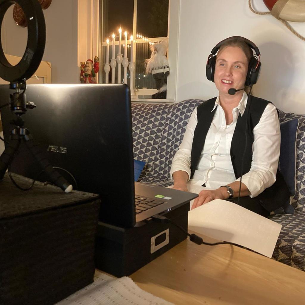 Jag föreläser digitalt sittandes i soffan hemma. Jag har på mig en svart väst, vit skjorta, headset med mikrofon. Framför mig till vänster syns en svart laptop och en videolampa. I bakgrunden står julpynt och ljusstakar i ett fönster.