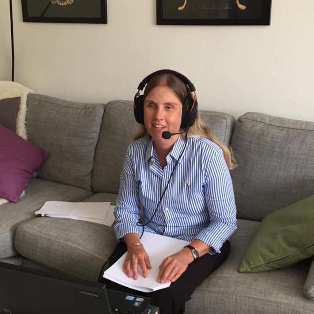 Jag med headset och mick i soffan med datorn framför mig på soffbordet