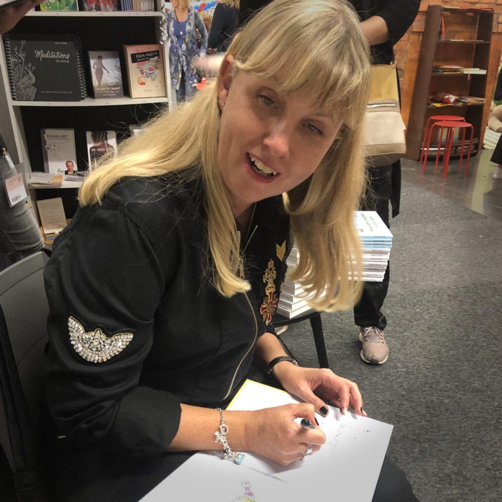 Jag sitter och signerar en öppen Fina fisken bok