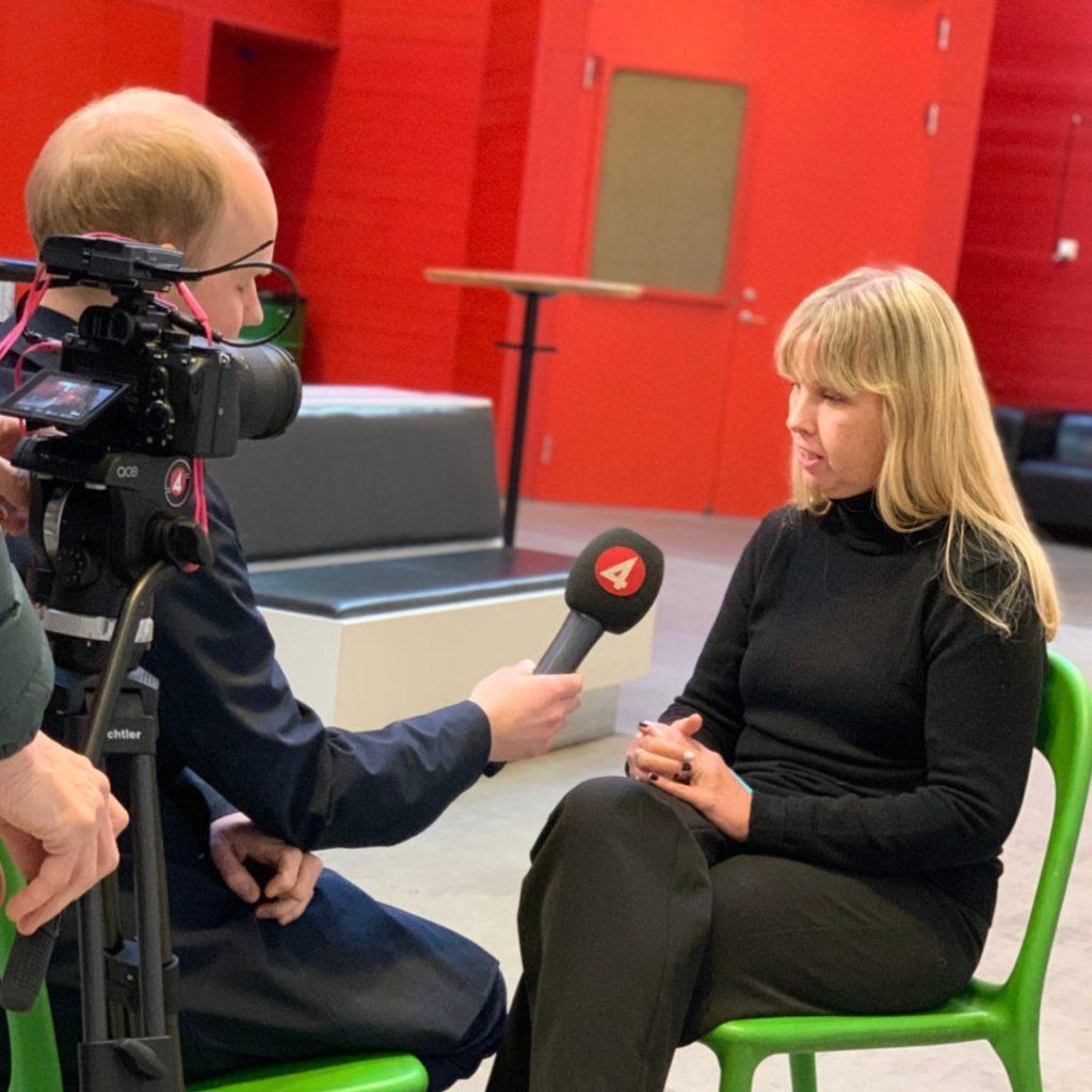 Jag iklädd helsvart sittandes i en intervju med en reporter från TV4. En kamera syns till vänster framför reporterns ansikte. Kameran och mikrofonen har röda TV4-logotyper. Vi sitter i ett stort öppet rum på färgstarka gröna plaststolar. Rummet har en ovanligt stark och tydlig röd nyans på väggen.