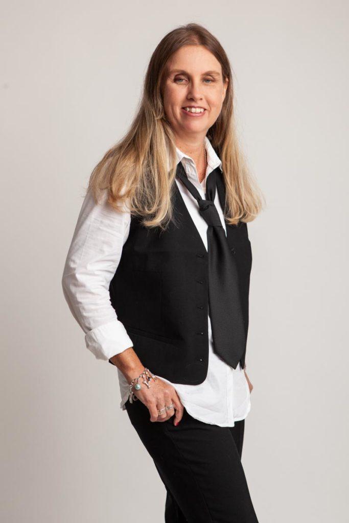 Profilbild på mig. Jag står i fotostudio med långt blont hår, klädd i svart väst, vit skjorta, slips, svarta byxor och tittar mot bilden med ett leende