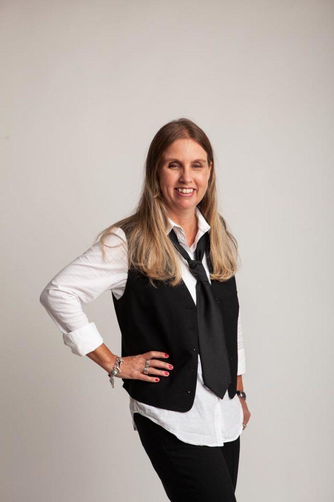 Profilbild på mig. Jag står i fotostudio med långt blont hår, klädd i svart väst, vit skjorta, slips, svarta byxor och tittar mot bilden med ett brett leende. Ena handen håller jag vinklat in mot midjan.