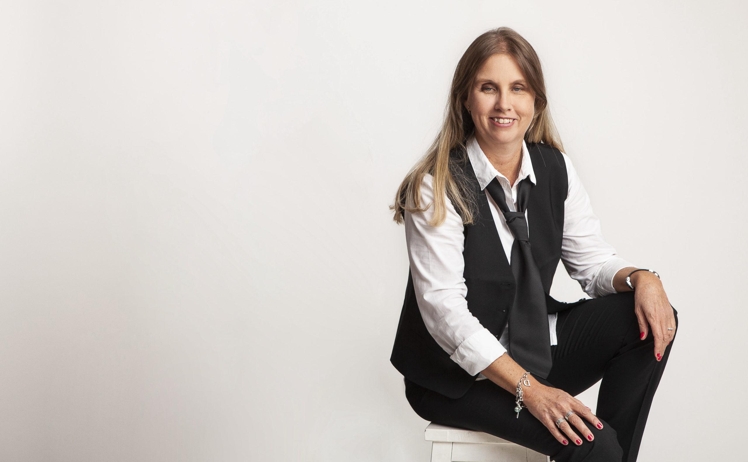 Profilbild på mig sittandes på en pall i fotostudio. Jag har långt blont hår, klädd i svart väst, vit skjorta, slips, svarta byxor och tittar mot bilden med ett leende