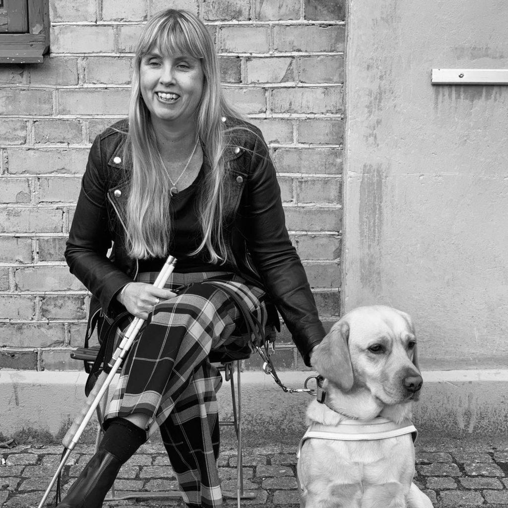 Svartvitt foto med mig sittandes bredvid min ledarhund, en ljus labrador iklädd vit sele. Jag har på mig svart skinnjacka, och rutiga byxor